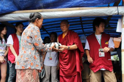 Khenpo tsethen give the donation packet to the poor  people
